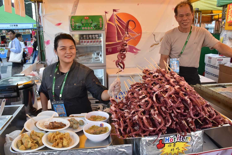 Macau Food Festival woman holding sticks of seafood